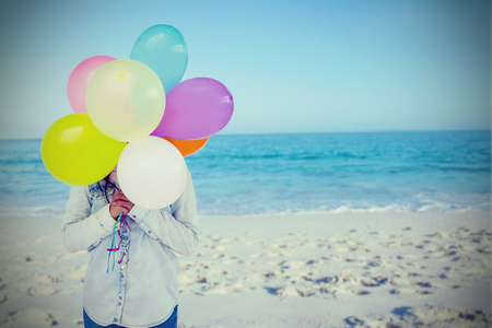 Woman hiding her face with bunch of colorful balloons  against beach against clear sky
