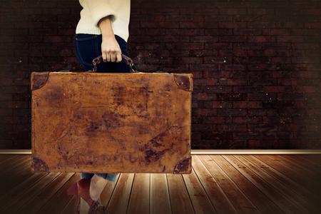 レンガの壁で部屋に対してヴィンテージ スーツケースを持った女性の低いセクション 写真素材