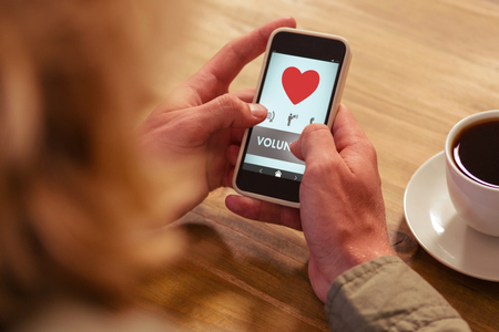 Volunteer text with heart shape against woman using phone at cafe Imagens