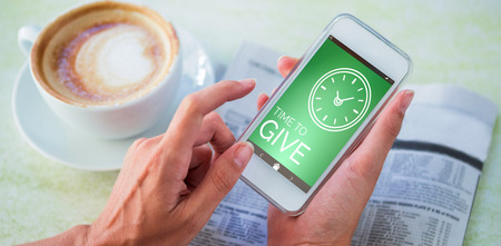 using smartphone: Digitally generated image of Time To Give text with clock icon against man using mobile phone by coffee and newspaper in cafe