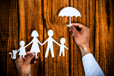 hand holding an umbrella and a family in paper against overhead of wooden planks Stok Fotoğraf