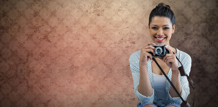 Portrait of happy young woman holding camera against room with wallpaper