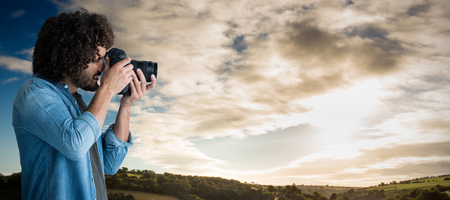 Male photographer taking picture with digital camera  against cloudy sky over countryside Stock Photo