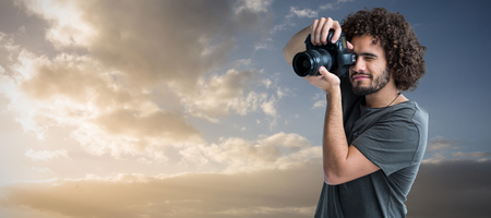 Young man photographing with digital camera  against cloudy sky landscape