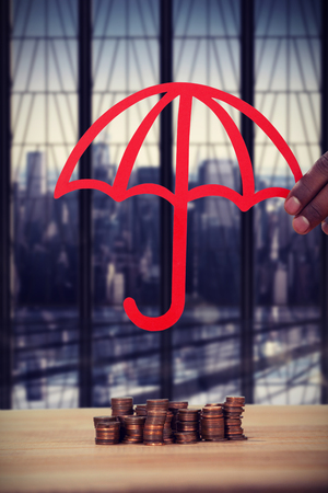 hand holding a red umbrella against room with large window looking on city