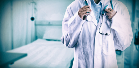scrolling: Asian doctor holding stethoscope against bed in clinic