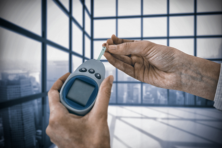 Close up of man hand testing blood sugar with glucometer against room with large window showing city