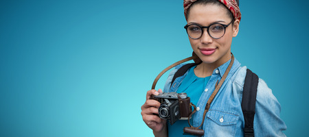 Portrait of female photographer with camera against blue vignette background