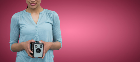 Portrait of female photographer holding vintage camera  against red and white background