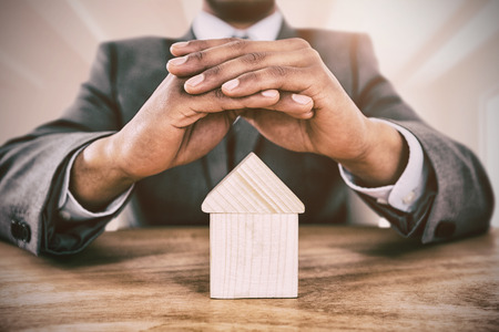 Businessman protecting house model with hands against bright white room Stock Photo