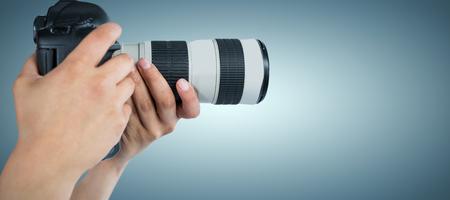 Cropped hands of photographer holding digital camera against grey vignette