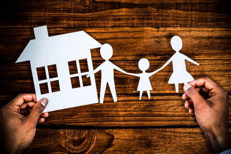 hands holding a family with her house in paper against overhead of wooden planks