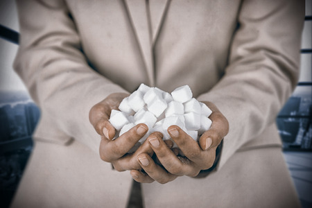 Womans hands cupped with sugar cubes against room with large window showing city Stock Photo