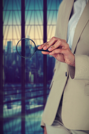 Midsection of businesswoman holding magnifying glass against room with large window looking on city