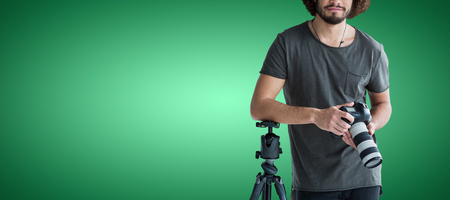 Portrait of young photographer holding digital camera against green vignette