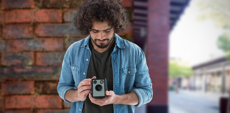 black and white photograph: Male photographer looking at vintage camera  against view of brick wall