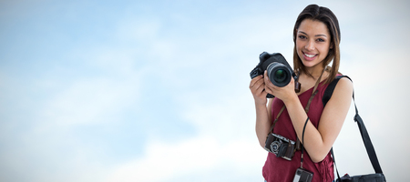 Portrait of happy young woman holding digital camera against blue sky with clouds