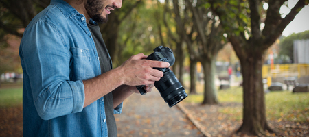 Smiling male photographer using camera  against footpath amidst trees at park Stock Photo