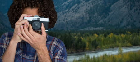rural road: Male photographer taking picture with camera against scenic view of mountains Stock Photo