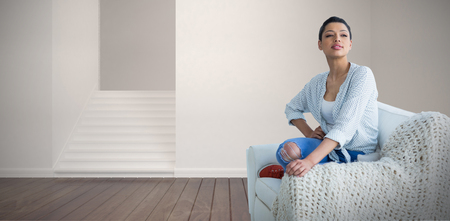 Young woman posing while sitting on sofa  against empty room