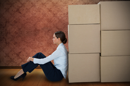run down: Businesswoman leaning on cardboard boxes against white background against grimy room