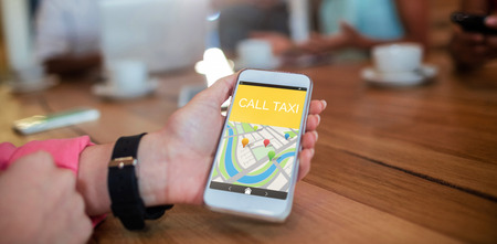 Digitally generated image of Call taxi text with map against woman holding mobile phone at table