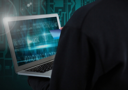 Digital composite of Hacker using a laptop and holding a credit card in front of digital background Stock Photo
