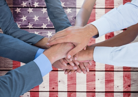 coworker: Digital composite of Business people with hands together against american flag Stock Photo