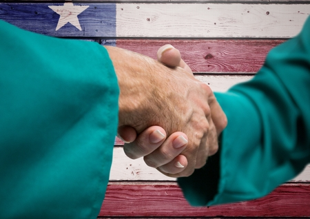 extending: Digital composite of Senior people shaking their hands against american flag