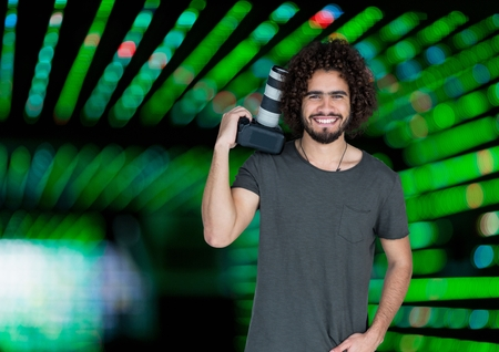 Digital composite of happy photographer with the camera rest on his shoulder. Green blurred lights  behind