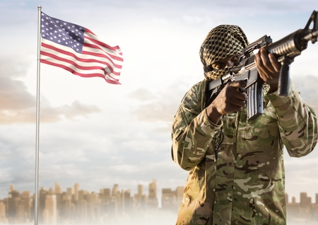 spangled: Digital composite of Military with covered face holding and pointing a weapon against american flag