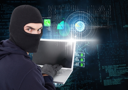 office theft: Digital composite of Hacker looking the lens and using a laptop in front of digital background