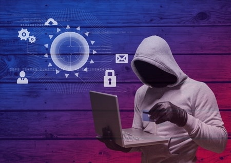 cyber defence: Digital composite of Hacker with hood holding a credit card and using a laptop in frond of wood background with digital i