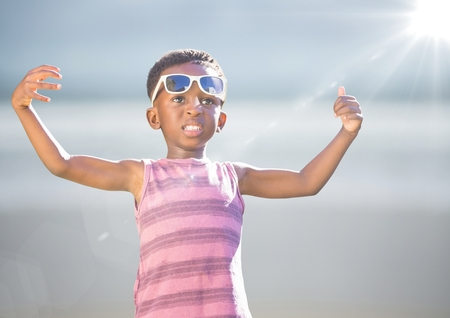 Digital composite of Boy in sunglasses hands out against blurry beach with flare Stock Photo