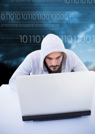 Digital composite of Hacker using a laptop in front of blue background with digital numbers