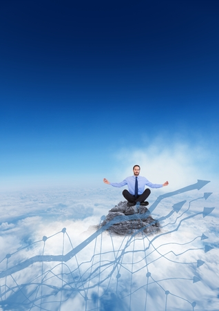 Digital composite of Business man meditating on mountain peak behind 3d blue graph