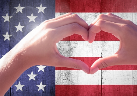 composite image: Digital composite of Hands showing a heart against american flag Stock Photo