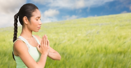 Digital composite of Woman meditating against blurry meadow on summer day Stock Photo