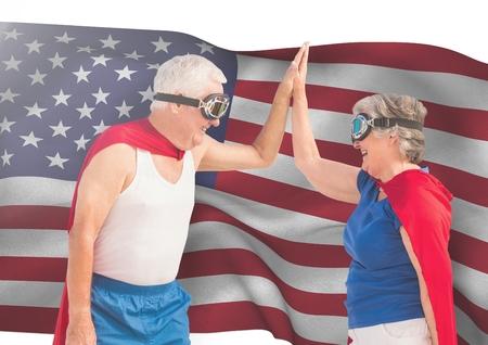 Digital composite of senior people high fiving against american flag