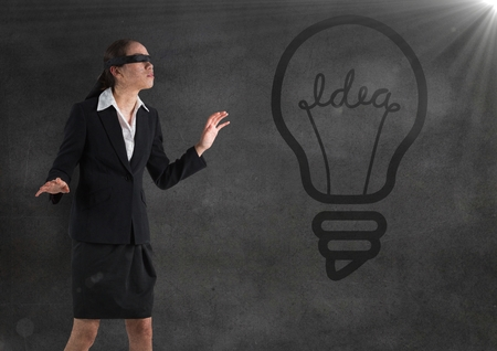 Digital composite of Blindfolded business woman against grey wall with 3d lightbulb graphic and flare