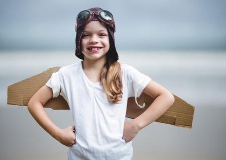 Digital composite of Girl in pilot costume against blurry beach