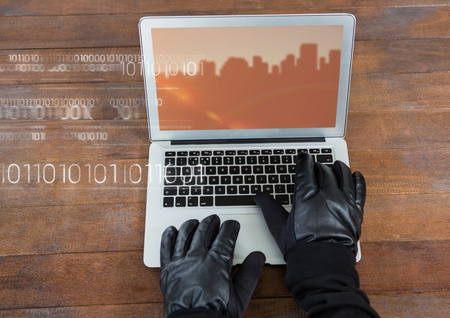 stealer: Digital composite of Hands typing on laptop with a screen with city buildings on wood table