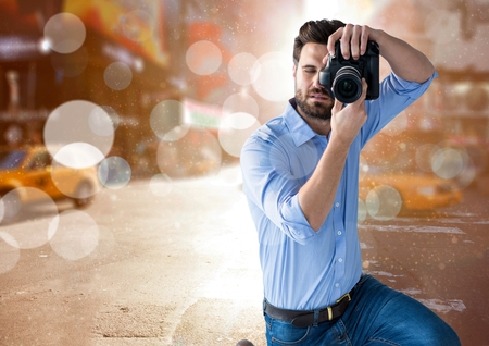 Digital composite of photographer taking a photo in te city with flares and blurred lights everywhere