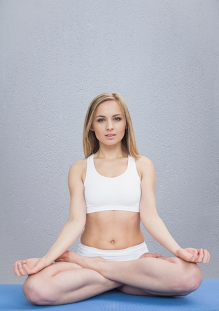 tough woman: Digital composite of Woman meditating against grey wall