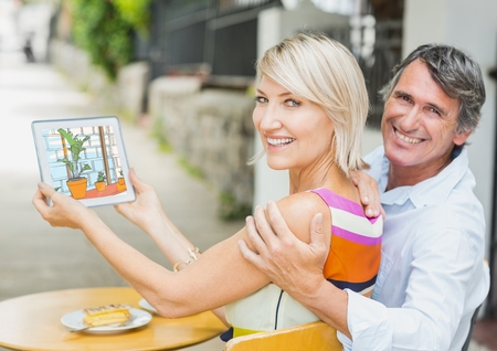 Digital composite of Happy couple showing the 3D design of the office with  tablet. ( color: blue, green and orange)