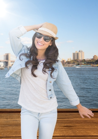 staircases: Digital composite of Woman with hand on summer hat against water and skyline with flare Stock Photo