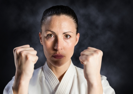 punched out: Digital composite of Woman in karate suit against mist