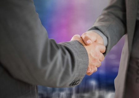Digital composite of Business handshake against blurry purple wall with city doodle Stock Photo