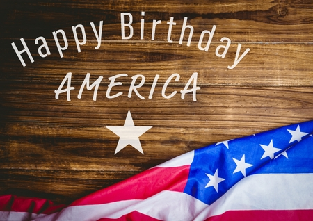 reach out: Digital composite of White fourth of July graphic against wood table and american flag Stock Photo