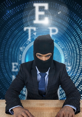 stealer: Digital composite of Hacker using a laptop in  a data center Stock Photo
